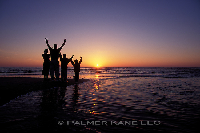 Silhouette of family on beach at sunrise raising their hands to the sun. Cape Fear, Bald Head Island, North Carolina, USA