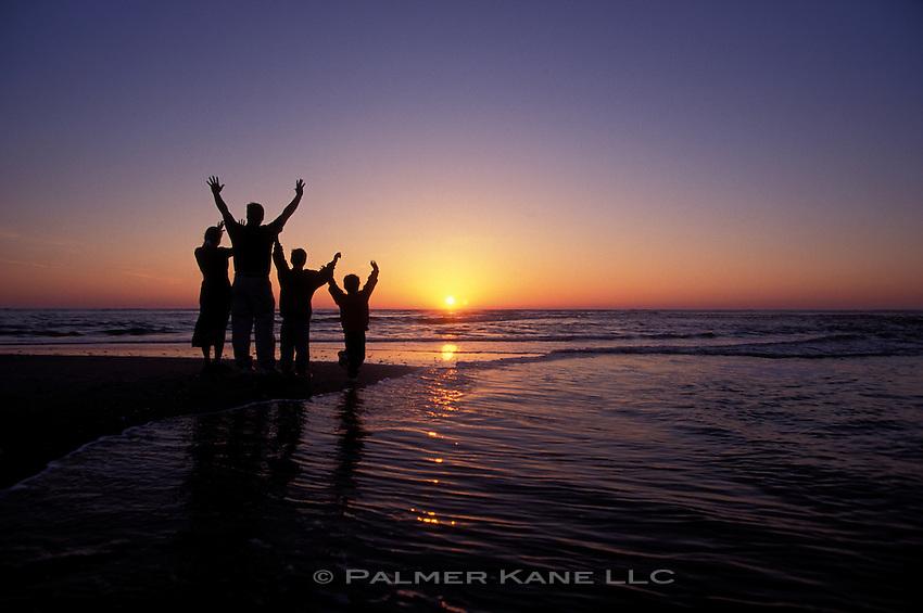 Silhouette of family on beach at sunrise raising their hands to the sun. Cape Fear, Bald Head Island, North Carolina, USA