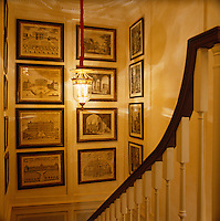 A collection of framed architectural drawings line the walls of the narrow staircase