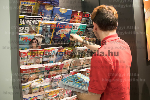 Salesman adjusts newspapers and magazines on the selves before the official opening ceremony of a new Spar food shop in downtown Budapest, Hungary on Aug. 22, 2018. ATTILA VOLGYI