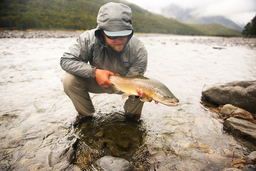 An angler hold a brown trout on a backcountry river on New Zealand's South Island.
