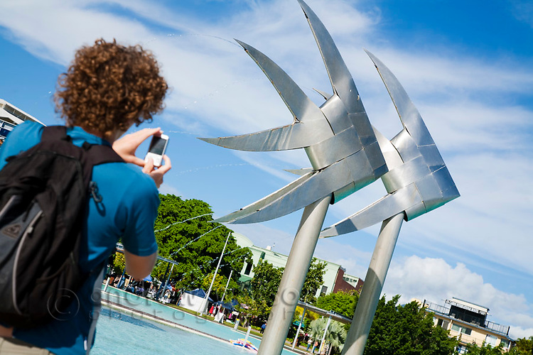 Tourist photographing the Fish Sculpture at the Esplanade lagoon.  Cairns, Queensland, Australia