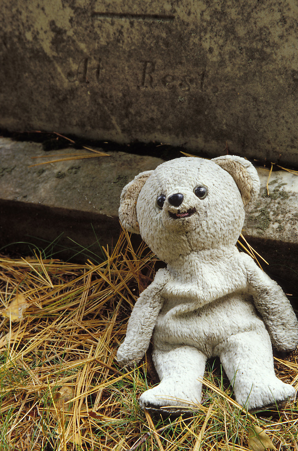 Teddy bear left at foot of tombstone, New York