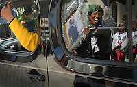 "Kelly.Jordan@jacksonville.com--011612--Veronica Price, of Jacksonville, is reflected in a window as she gets a ""thumbs up"" from a passing parade float as she holds up her hand made tribute sign to Dr. Martin Luther King Jr. during the annual Martin Luther King Jr. Day parade through downtown Monday January 16, 2012.(The Florida Times-Union, Kelly Jordan)"