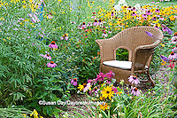 63821-206.10  Wicker chair and birdhouse  in garden with Black-eyed Susans (Rudbeckia hirta) Butterfly Bush (Buddleia davidii), Purple Coneflowers (Echinacea purpurea), Gray-headed Coneflowers (Ratibida pinnata) and Pink Bee balm (Monarda fistulosa) Marion Co, IL