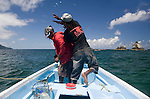 Two young fisherman throwing live bait from a pirogue, St Giles Island, Tobago