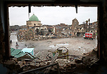 A Coca-Cola truck nearby, the ruins of the Great Mosque of al-Nuri on November 30, 2018, in the Old City of Mosul, Iraq, seen through the window of a war-damaged house nearby. Built over 800 years ago, the mosque was blown up by ISIS combatants during the final moments of the 2017 Battle of Mosul.