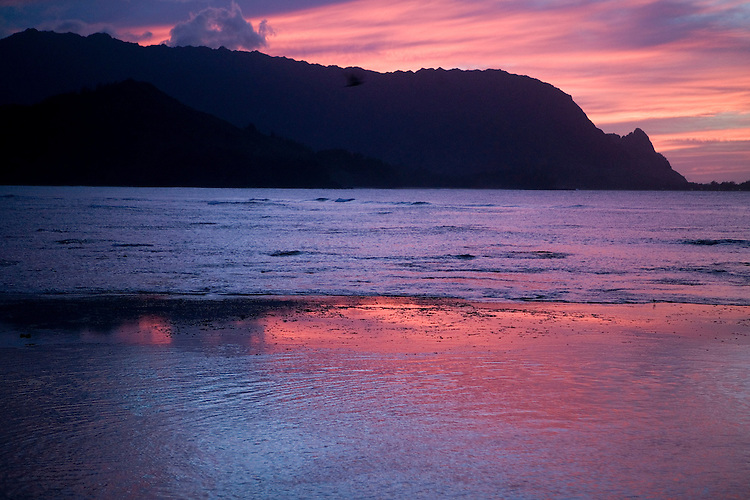 """The view of the sunset across Hanalei Bay to """"Bali Hai"""" from the public beach below the Princeville Resort"""