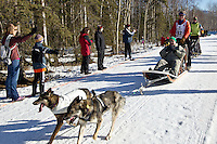 Linwood Fiedler and team run past spectators on the bike/ski trail during the Anchorage ceremonial start during the 2014 Iditarod race.<br /> Photo by Britt Coon/IditarodPhotos.com