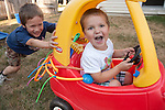 "When I called out the obligatory ""Be careful!"" my older son, age six, left, told me that it was okay, he had created a seat belt for his brother, age three, out of a sprinkler toy. I'm not sure why there was a sharp pointy stick tucked into the other side. The boys were in the backyard of our new house, playing a game they invented called ""Mater Tater Tater,"" where one person spins the car around wildly while the other rides."