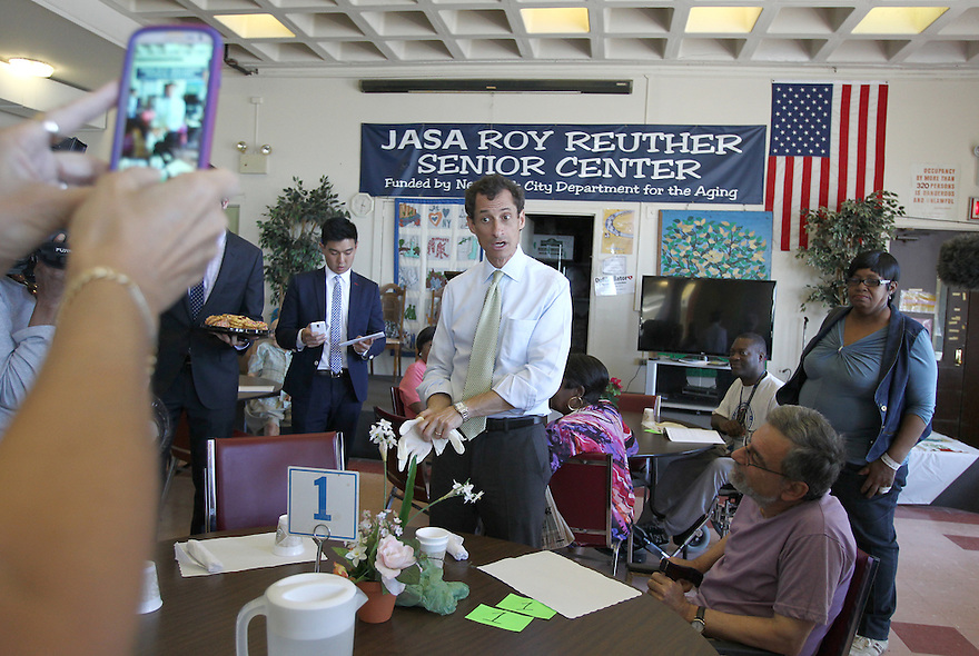 Anthony Weiner hands out cookies to seniors during a visit to the JASA Roy Reuther Senior Center on Wednesday, August 14, 2013 in New York. (AP Photo/ Donald Traill)