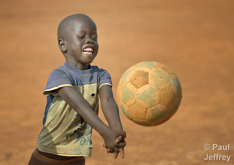A boy plays volleyball inside a camp for internally displaced families in Yei, South Sudan. The camp holds Nuer families who took refuge there in December 2013 after a political dispute within the country's ruling party quickly fractured the young nation along ethnic and tribal lines. The ACT Alliance is providing psycho-social services in the camp, including safe places for children to enjoy being children.