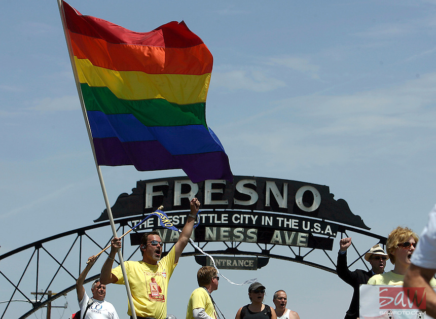 """FRESNO,CA - May 30,2009: Cheering as marchers arrive in downtown Fresno, Chip Garcia-Coakley, with flag, joins other activists representing Gay Rights Movement, as they cheer the arrival of marchers from Selma, CA to Fresno, CA, May 30, 2009. The group joined a rally at Fresno City hall. Gay rights activists are converging on Fresno today for a rally called """" Meet in the middle 4 equality."""""""