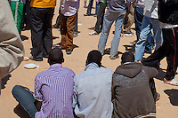 Tunisie RasDjir Camp UNHCR de refugies libyens a la frontiere entre Tunisie et Libye ....Tunisia Rasdjir UNHCR refugees camp  Tunisian and Libyan border  Tunisia campo profughi di Djiba al confine tra tunisia e Libia  trois refugies assis de dos, tre profughi seduti, di schiena