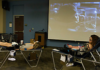 NWA Democrat-Gazette/CHARLIE KAIJO Taylor Fosbender of Rogers and MakaLee Dolney Of Little Flock rest after giving blood while ET plays on a projector on Thursday, October 12, 2017 at Northwest Arkansas Community College in Bentonville. The Community Blood Center of the Ozarks took donations at the college's student union.