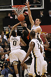 Miami (Fl) Hurricanes guard Garrius Adams (25) is stuck in the middle of a Wake defense led by Wake Forest Demon Deacons center Carson Desrosiers (33) and Wake Forest Demon Deacons guard J.T. Terrell (0). The score is tied at the half 37-37.