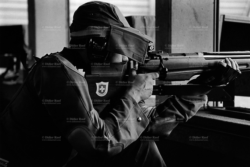 Switzerland. Canton Geneva. Geneva. St-Georges shooting range. Exercises de l'Arquebuse et de la Navigation is a shooting sports' association. A member of a swiss riflemen's association aim his rifle on target during the memorial shooting for « L'escalade ». A sticker with a swiss flag on the rifle butt. L'Escalade, or Fête de l'Escalade (from escalade, the act of scaling defensive walls), is an annual festival held in Geneva, celebrating the defeat of the surprise attack by troops sent by Charles Emmanuel I, Duke of Savoy during the night of 11–12 December 1602. A shooting range or firing range or pistol range or rifle range or shooting gallery or shooting ground is a specialized facility designed for firearms practice. The flag of Switzerland consists of a red flag with a white cross (a bold, equilateral cross) in the centre. It is one of only two square sovereign-state flags. 21.10.2017 © 2017 Didier Ruef