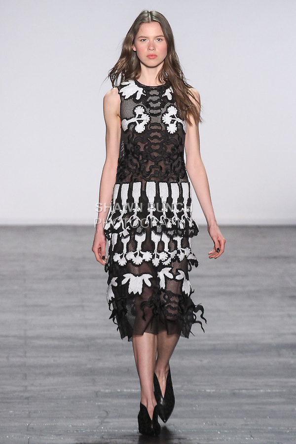 """Model Kira walks runway in a mesh sleeveless dress with Eight Treassure applique in black, from the Vivienne Tam Fall Winter 2016 """"Cultural Dreamland The New Silk Road"""" collection, presented at NYFW: The Shows Fall 2016, during New York Fashion Week Fall 2016."""