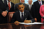 United States President Barack Obama (C) signs the Fair Sentencing Act beside a bipartisan group of lawmakers in the Oval Office of the White House, in Washington DC, USA, Tuesday, 03 August 2010. The law will aim to correct the disparities between crack and powder cocaine sentencing.  Previously, people in possession of powder cocaine could carry up to one hundred times more grams than crack offenders and receive the same sentence.  .Credit: Michael Reynolds - Pool via CNP