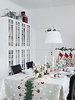 A spotty tablecloth, vases of fresh flowers, candles and cheery decorations have created a thoroughly festive table display