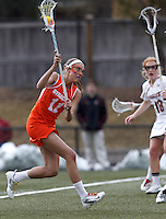 Syracuse University midfielder Amy Cross (11) takes a shot.  Syracuse University (orange) defeated Boston College (white), 17-12, on the Newton Campus Lacrosse Field at Boston College, on March 27, 2013.