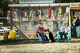 USA, Alaska, Ketchikan, a couple sits outside of Dockside Galley Restaurant with their dog near Behm Canal and Knudsen Cove along the Tongass Narrows