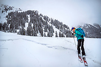 A woman skier stands looking back with a look of playful fear at a huge fracture ine in the snow. In Kyrgyzstan, the snow fractures very easily and is a huge concern for avalanche risk, in this case it is very low angle.