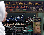 4 APRIL 2012, Kabul, Afghanistan:  A young Afghan girl walks by a beauty salon. The many salons around the city  feature western women on the posters with little resemblance to local dress codes. Picture by Graham Crouch/The Australian