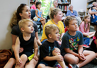 NWA Democrat-Gazette/CHARLIE KAIJO (From left) Abbey O&Otilde;Bryan of Bella Vista and her two sons Sinclair O'Bryan, 2 and A.J. O'Bryan, 5 watch a magic show, Thursday, July 5, 2018 at the Bella Vista Public Library in Bella Vista. <br /><br />Tommy Terrific performed a musical magic show for youth.