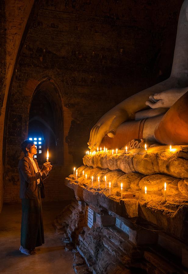 BAGAN, MYANMAR - CIRCA DECEMBER 2013: Pilgrim paying tribute to Buda in the Pahto Thamya Temple in Bagan