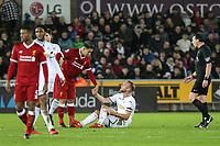 Roberto Firmino of Liverpool  helps up Mike van der Hoorn of Swansea City during the Premier League match between Swansea City and Liverpool at the Liberty Stadium, Swansea, Wales on 22 January 2018. Photo by Mark Hawkins / PRiME Media Images.