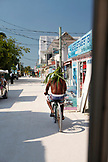 BELIZE, Caye Caulker, a man rides down main street in his hand made palm leaf hat
