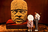 Two visitors admiring the stone sculptured head of an olmec in the Museum of Antropology in Mexico City