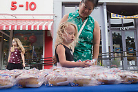 NWA Democrat-Gazette/CHARLIE KAIJO Annabella Bury (center) and Hoa Bury of Bentonville grab treats, Monday, June 3, 2019 at the downtown square in Bentonville<br />