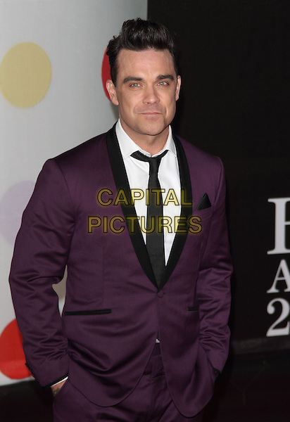 Robbie Williams.Arrivals for The 2013 Brit Awards at the O2 Arena, London, England..February 20th 2013.BRITS  half length purple suit black tie lapel white shirt hands in pockets .CAP/ROS.©Steve Ross/Capital Pictures