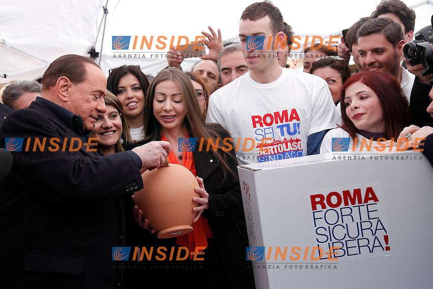 Silvio Berlusconi vota al gazebo del Pantheon. Non avendo soldi con se, la sua guardia del corpo gli da 50E che infila nel salvadanaio del Gazebo<br /> Silvio Berlusconi votes at the Gazebo of Pantheon. As he doesn't have money with him, his bodyguard gives him 50E to finance the party<br /> Roma 12-03-2016 Gazebo al Pantheon. Gazebarie del centro destra per valutare il gradimento del candidato proprosto a Sindaco di Roma.<br /> Gazebo at Pantheon. Primary elections of the Centre-right party for the local elections of the Mayor of Rome.<br /> Photo Samantha Zucchi Insidefoto