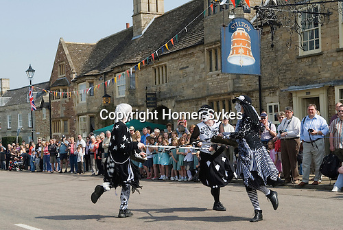 "May Fair  Stilton village.  Cambridgeshire UK 2008. ""Pig Dykes Molly"" Morris Dancers performing a ""broom dance"""
