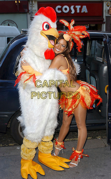 JODIE MARSH & CHICKEN.Helps launch the new PETA ad campaign urging tube riders to say no to nuggets. Jodie travelled from Oxford Street to Liverpool Street informing passengers how millions of chickens suffer every year before being slaughtered. .November 7th, 2005 .Ref: BEL.full length orange yellow feather hat bikini top skirt hug embrace gesture costume dress up.www.capitalpictures.com.sales@capitalpictures.com.© Capital Pictures.