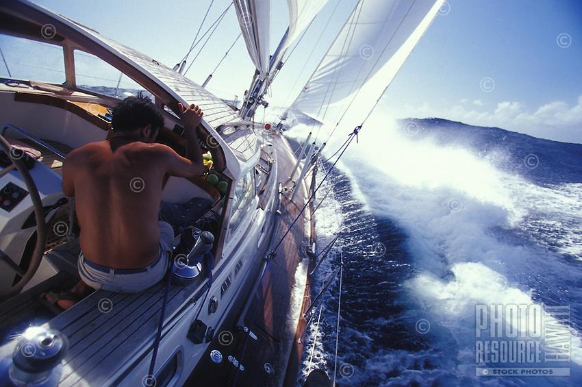 Man sailing to windward in rough seas on the Halberg-Rassy 46 yacht 'Heron', Pacific Ocean, Tahiti, French Polynesia