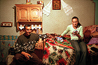 ROMANIA / Maramures / Budesti / 28.08.2006..Anuta Tibil, 16, checks for text messages on her mobile phone while her father, Vasilya, 47, watches satellite television. In the lead up to joining the European Union in 2007, Romania underwent dramatic technolgical changes and nowhere is this more evident than in Maramures. Land line telephones only began arriving at homes in 2001-2002, yet mobile service followed soon after and since 2005 it has become obligatory for the youth to have the latest mobile phones. Just a few years ago one had to walk or travel by horse cart as many as 10 kilometers to speak with a friend, but today, youth in Maramures converse like teenagers anywhere else in the world. Satellite television descended upon the region in 2006, when companies finally made it cheap enough for peasants to sign up for the basic 100 channel package. Now, even traditional, carved, wooden homes are marked by small satellite dishes affixed to their front porches or rooves. The internet is sure to follow soon. Maramures has experiended more change since the year 2000 than in the entire previous millenium...© Davin Ellicson / Anzenberger