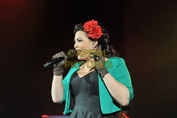Caro Emerald (Caroline Esmeralda van der Leeuw).performing live in concert, Shepherd's Bush Empire, London, England..13th December 2011.on stage gig performance music half length black dress green jacket gloves flower in hair red singing  profile.CAP/MAR.© Martin Harris/Capital Pictures.