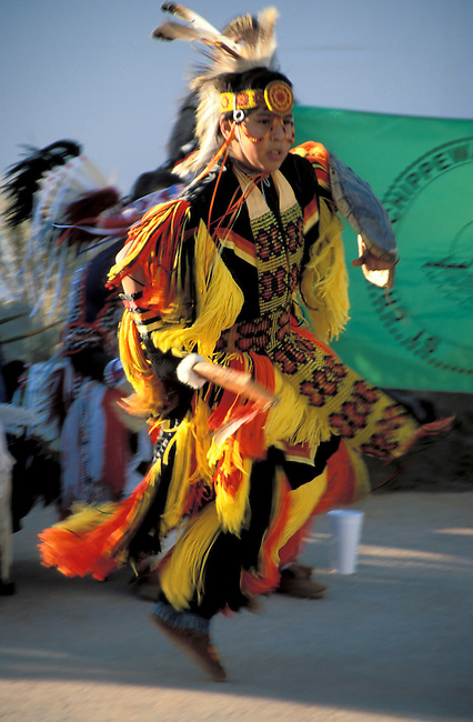 Chippewa boy  dressed in his pow wow regalia demonstrates a grass dance during the Olympics.
