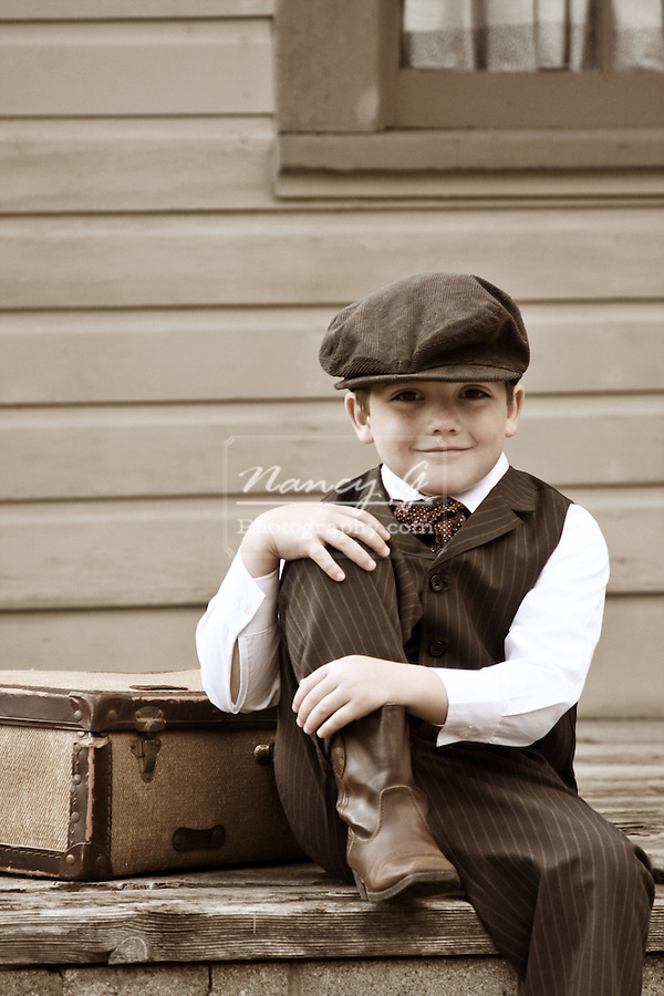 A young boy sitting on the train depot platform