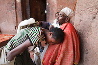 Coptic Orthodox priest blesses the pilgrim touching his back with the cross in Lalibela Ethiopia