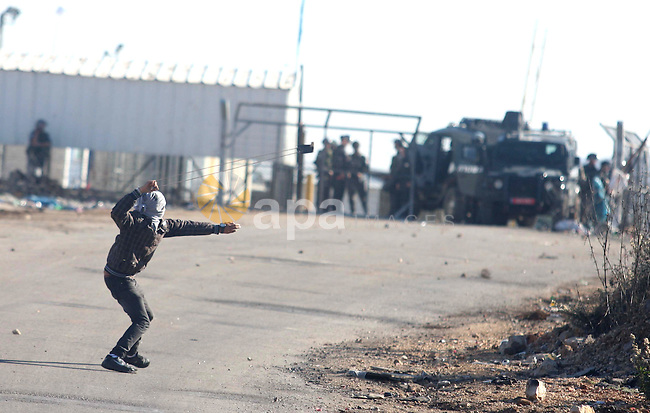 A Palestinian protester throws stones at Israeli troops during clashes against Israel's operations in Gaza Strip, outside Ofer, an Israeli military prison near the West Bank city of Ramallah, Thursday, Nov. 15, 2012. Meanwhile, Palestinian President Mahmoud Abbas cut short a trip to Europe to deal with the crisis. Photo by Issam Rimawi