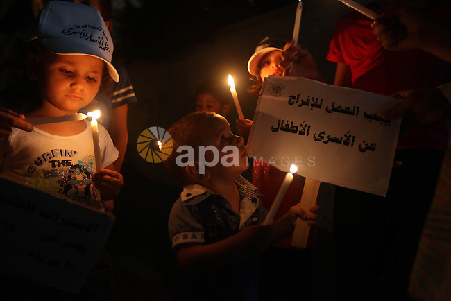 Palestinian children light candles during a rally in solidarity with prisoners in Israeli jails, in front of  the Red Cross' offices  in Gaza city, September 08, 2012. Photo by Majdi Fathi