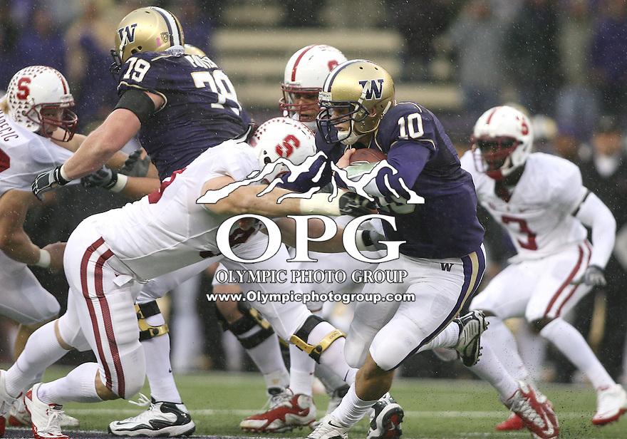 Oct 30, 20010:  Washington quarterback #10 Jake Locker scrambles past a diving #95 Brian Bulcke of Stanford.  Stanford defeated Washington 41-0 at Husky Stadium in Seattle, Washington.