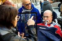Roma 4 Novembre  2014.<br /> Manifestazione davanti al ministero dell'Economia del Comitato 16 Novembre, associazione di persone malate di Sla e loro famigliari, per chiedere il ripristino del fondo della non autosufficienza  ridotto a 250 milioni con la legge di Stabilit&agrave;, non solo torni a 350 milioni ma venga aumentato a un miliardo. Un famigliare comunica con un ammalato di Sla con la Tavola di Comunicazione<br /> Rome November 4, 2014. <br /> Demonstration in front of the Ministry of Economy Committee November 16, an association of people sick  with ALS and their families, to ask for the restoration fund of self-sufficiency reduced to 250 million by the law of stability, not only back to 350 million but is increased one billion. A family communicates with a patient with ALS with the Table of Communication