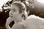 Girl wearing Angel Wings, with sun flare, in antique sepia, taken at Levy Park and Preserve, Merrick, Long Island, New York, USA, 2010