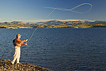 Man fly fishing along the desert shoreline of Lake Pleasant with the foothills of the Bradshaw Mountains in the distance.